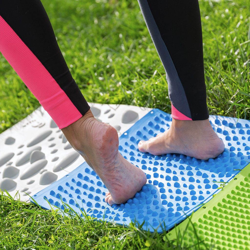 Close up piedi e Yowal, texture di yowalk sulla pianta del piede; ragazza utilizza yowalk sul prato